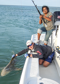 shark fishing guide helping an angler boat a shark